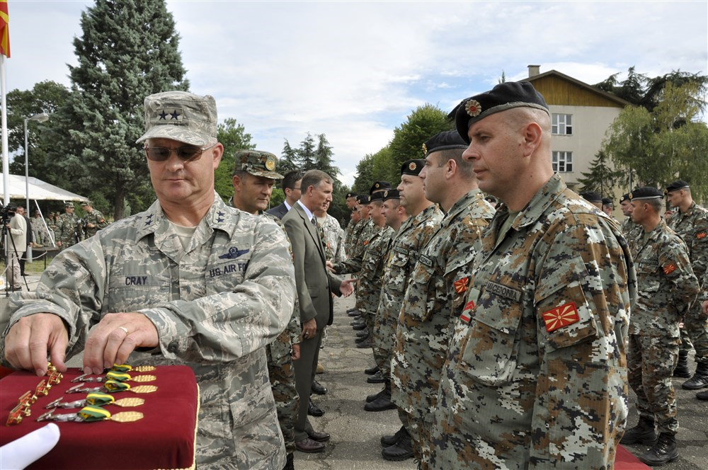 U.S. Air Force Maj. Gen. Steven Cray, the adjutant general of the Vermont National Guard, pins a medal on one of 79 soldiers from the army of Macedonia
